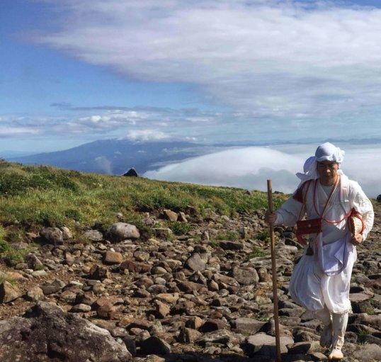Yamabushi training on Mt. Gassan of the Dewa Sanzan with Mt. Chokai in the background